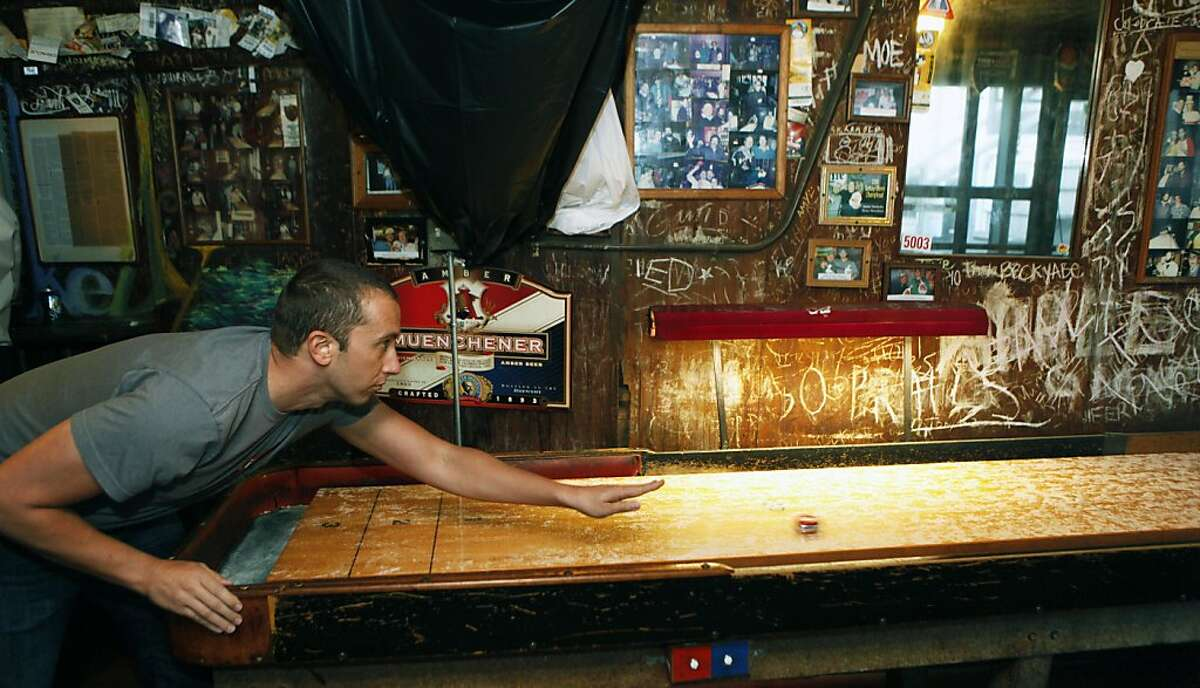 Bryan Maas from Oakland enjoys a game of shuffleboard at the Kingfish. Emil Peinert owner of the Kingfish pub and Cafe has filed to make his very beloved watering hole a Oakland landmark Thursday October 6, 2011.