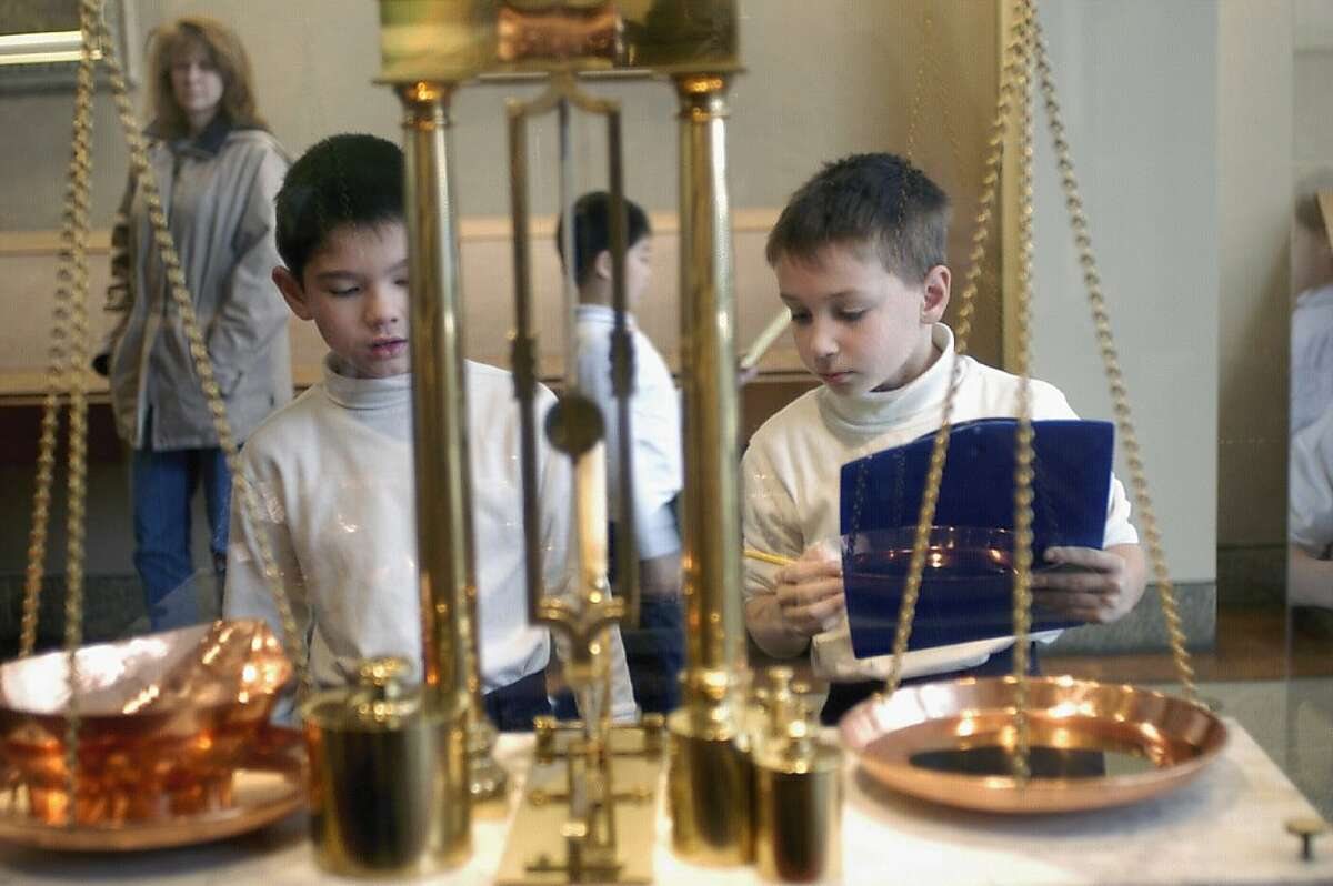 Boys looking at authentic scales used in a Wells Fargo office to weigh gold during the Gold Rush. Those are real gold nuggets on the scale.