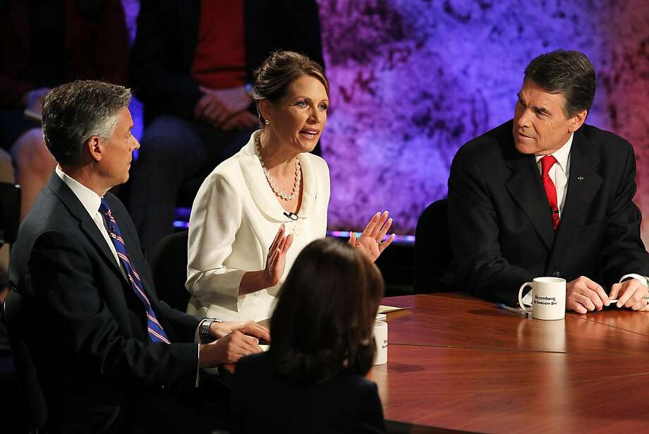 HANOVER, NH - OCTOBER 11:  Former Utah Gov. Jon Huntsman (L) and Texas Gov. Rick Perry (R) look on as U.S. Rep. Michele Bachmann (R-MN) (C) speaks during the Republican Presidential debate hosted by Bloomberg and the Washington Post on October 11, 2011 at Dartmouth College in Hanover, New Hampshire. Eight GOP candidates met for the first debate of the 2012 campaign focusing solely on the economy.  (Photo by Justin Sullivan/Getty Images) Photo: Justin Sullivan, Getty Images