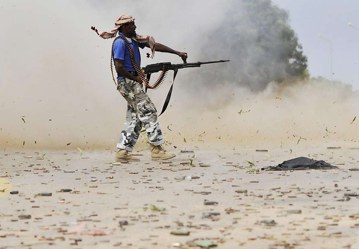 A Libyan revolutionary fighter fires his machinegun while attacking pro-Gadhafi forces inside the Ouagadougou conference center of Sirte, Libya, Friday, Oct. 7, 2011. Rebel forces have besieged Sirte since September 15 but have not managed to penetrate the heart of the city because of fierce resistance from loyalists inside the home town of Libya's ousted leader Moammar Gadhafi. (AP Photo/Bela Szandelszky)