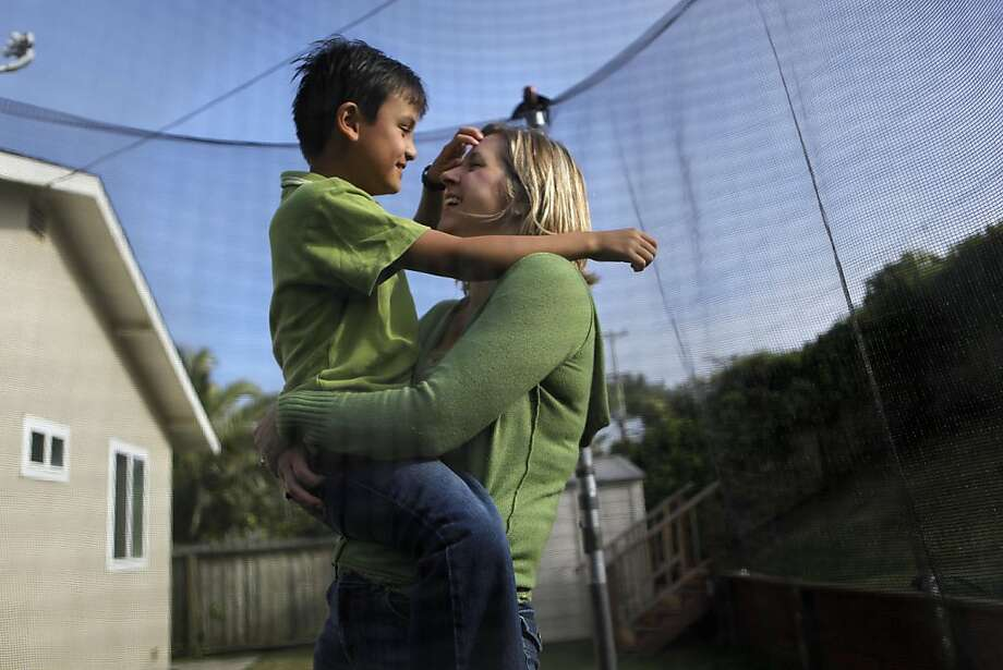 Lisa Valerio and her 8-year-old autistic son Nathan play on a trampoline in the backyard of their San Bruno, Ca. home, Tuesday October 11, 2011.  A bill governor Jerry Brown signed in law on Sunday will require health insurers to provide behavioral therapy, considered the most promising treatment to date, for people with autism. While the new law will help many parents who have struggled with getting care for their kids, it my be only a stop-gap measure. Photo: Michael Macor, The Chronicle