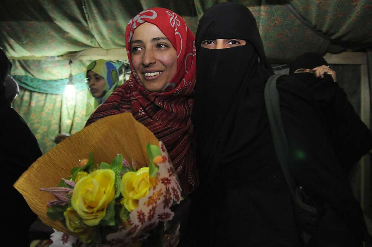 Tawakkol Karman, a pro-democracy campaigner, receives congratulations from a supporter at Tagheer Square in Sanaa, Yemen, Oct. 7, 2011. Karman was awarded the Nobel Peace Prize for 2011 on Friday, along with President Ellen Johnson Sirleaf of Liberia ? Africa's first elected female president ? and Liberian peace activist Leymah Gbowee. (Amira Al-Shariff/The New York Times) Ran on: 10-08-2011 Tawakkul Karman (left), a human rights activist, celebrates news of her Nobel Prize in Change Square in Sanaa, Yemen.