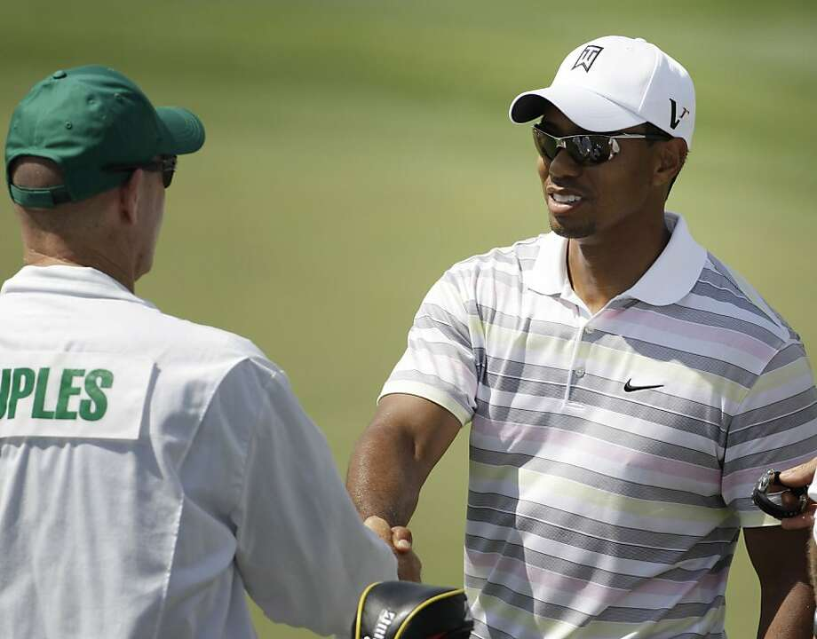 In this April 5, 2010, photo, Tiger Woods shakes hands with Fred Couples' caddie, Joe LaCava, during a practice round for the Masters golf tournament in Augusta, Ga. Woods has hired LaCava to be his caddie. Two people aware of the deal told The Associated Press on Sunday, Sept. 25, 2011, that LaCava decided to leave Dustin Johnson, one of the most talented young Americans, to go to work for Woods. (AP Photo/David J. Phillip) Photo: David J. Phillip, AP
