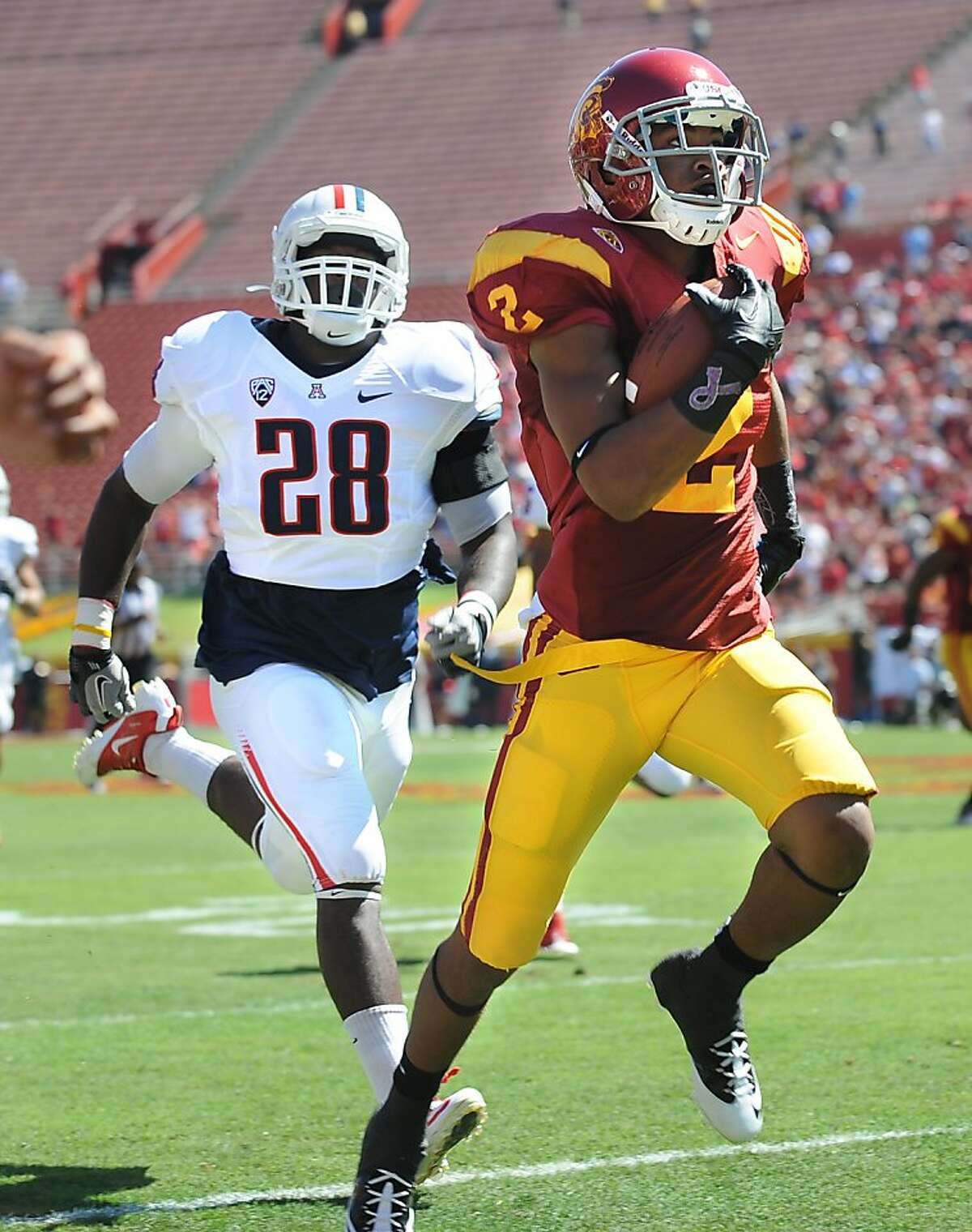 University of Southern California receiver Robert Woods, right, beats Arizona defensive end C.J. Parish to the end zone for an 82-yard touchdown catch in the first quarter at the Los Angeles Coliseum in Los Angeles, California, on Saturday, October 1, 2011. USC outslugged Arizona, 48-41. (Wally Skalij/Los Angeles Times/MCT)