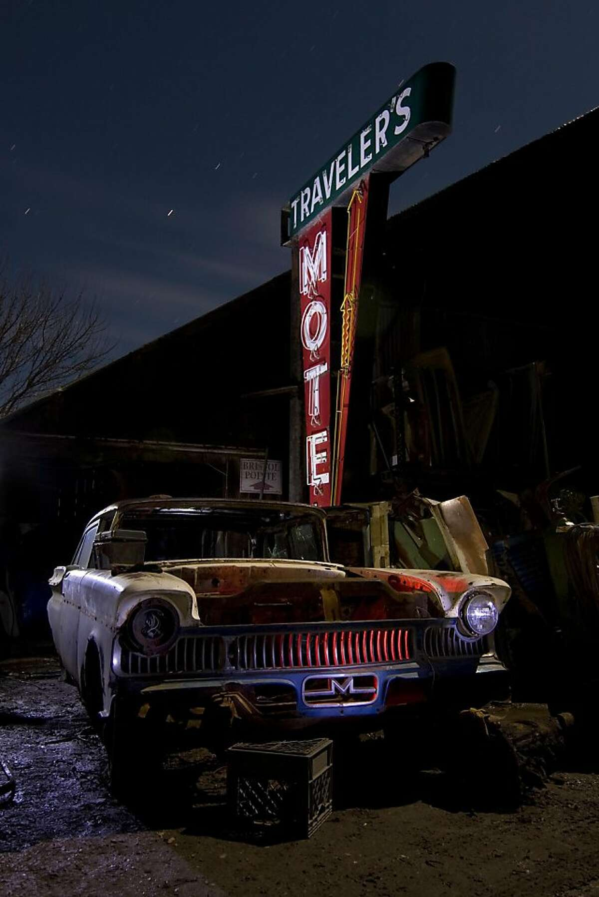 """Employing a technique known as """"light painting,"""" Troy Paiva illuminates his subjects-typically discarded automobiles-with flashlights fitted with colored gel filters. This process lends his photographs their distinctive, neon-tinged artificiality. This photo was taken in 2011."""