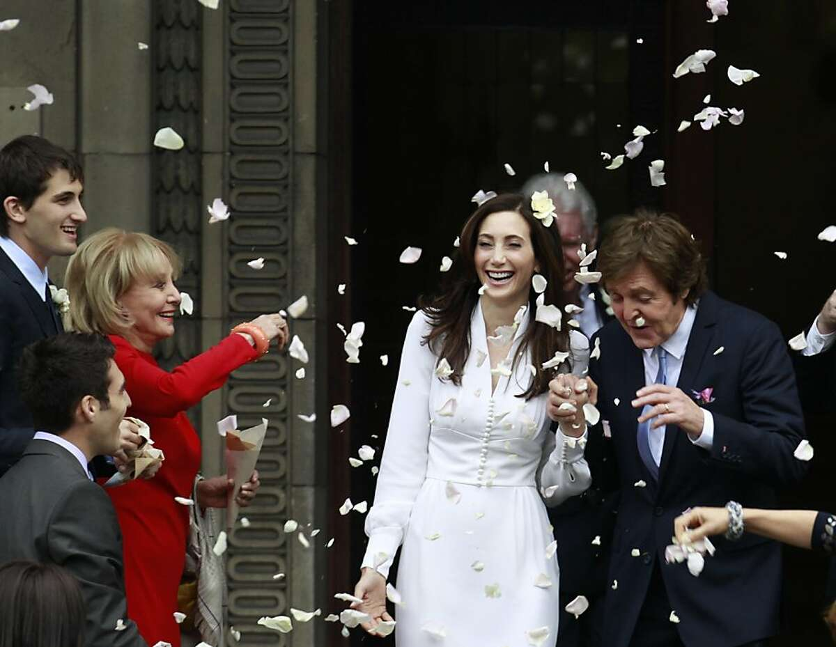 American broadcast journalist and author Barbara Walters throws rose petals as former Beatle Sir Paul McCartney and his wife American heiress Nancy Shevell leave Marylebone Registry Office, following their wedding in central London , Sunday Oct. 9, 2011. Shevell, 51, is McCartney's third wife.The couple met in the Hamptons in Long Island, New York, shortly after the singer's divorce from Heather Mills in 2008 and they were engaged earlier this year. (AP Photo/Lefteris Pitarakis)