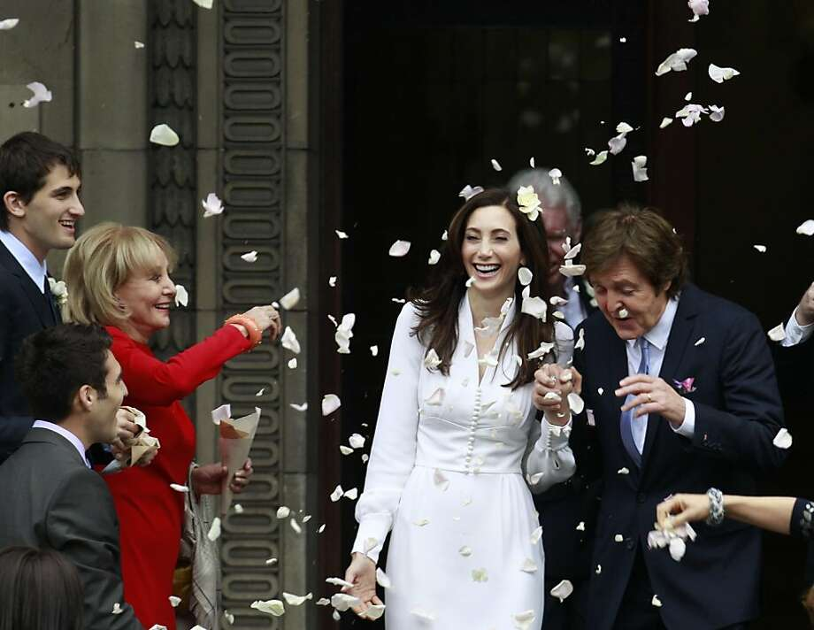 American broadcast journalist and author Barbara Walters throws rose petals as former Beatle Sir Paul McCartney and his wife American heiress Nancy Shevell leave Marylebone Registry Office, following their wedding in central London , Sunday Oct. 9, 2011.  Shevell, 51, is McCartney's third wife.The couple met in the Hamptons in Long Island, New York, shortly after the singer's divorce from Heather Mills in 2008 and they were engaged earlier this year. (AP Photo/Lefteris Pitarakis) Photo: Lefteris Pitarakis, AP