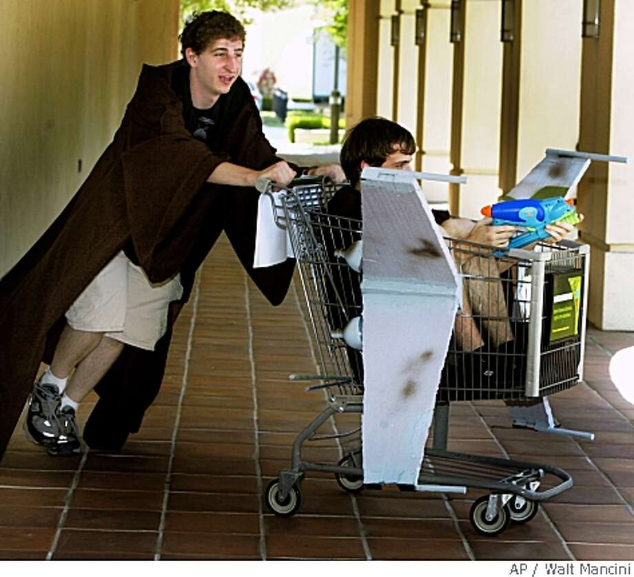 """Oren Hazi pushes a grocery cart decorated as an a X-Wing fighter from a Star Wars movie, with pilot Cliff Blakestae squirt gunning targets around the Caltech campus in Pasadena, Calif., during Ditch Day on Wednesday, May 21, 2008.  Caltech seniors held their annual Ditch Day which involves seniors creating elaborate """"traps', turning their dorm rooms into puzzles that under-classman must solve. (AP Photo/San Gabriel Valley Tribune, Walt Mancini) Photo: Walt Mancini, AP"""