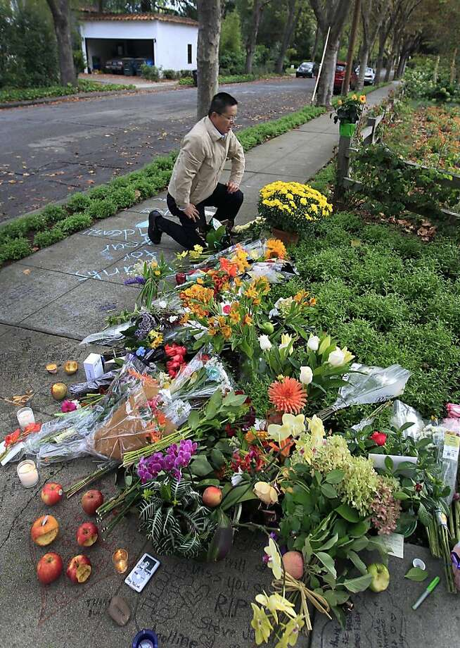 Wanfeng Shang leaves flowers at a memorial outside the home of Steve Jobs, co-founder and former chief executive officer of Apple Inc., in Palo Alto, California, U.S., on Thursday, Oct. 6, 2011. Jobs, who built the world's most valuable technology company by creating devices that changed how people use electronics and revolutionized the computer, music and mobile-phone industries, died. He was 56. Photographer: Tony Avelar/Bloomberg *** Local Caption *** Wanfeng Shang Photo: Tony Avelar, Bloomberg
