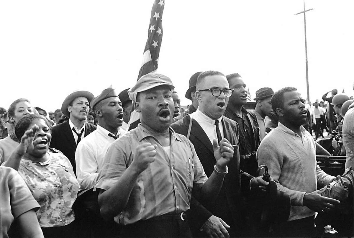 Martin Luther King leads singing marchers toward Montgomery during the Selma March, 1965. On right, SNCC Chairman, John Lewis