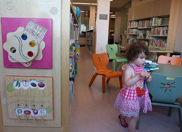 Emma Berlin, 2 and a half years old, passing one of the new Play-to-Learn interactive walls of Potrero Branch Library in San Francisco, California, on Friday, September 23, 2011. Photo: Liz Hafalia, The Chronicle