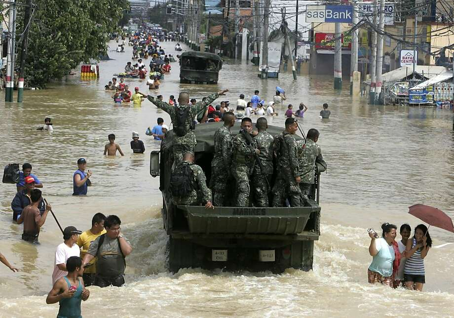 CORRECTS TO FOURTH DAY IN FIRST SENTENCE - Philippine Marines drive through floodwaters to help in rescue efforts as flooding continues for the fourth day Sunday Oct. 2, 2011 at Calumpit township, Bulacan province north of Manila, Philippines.  Back-to-back typhoons have left at least 55 people dead and rescuers scrambling to deliver food and water to hundreds of villagers marooned on rooftops for four days by flood in the northern Philippines.  (AP Photo/Bullit Marquez) Photo: Bullit Marquez, AP