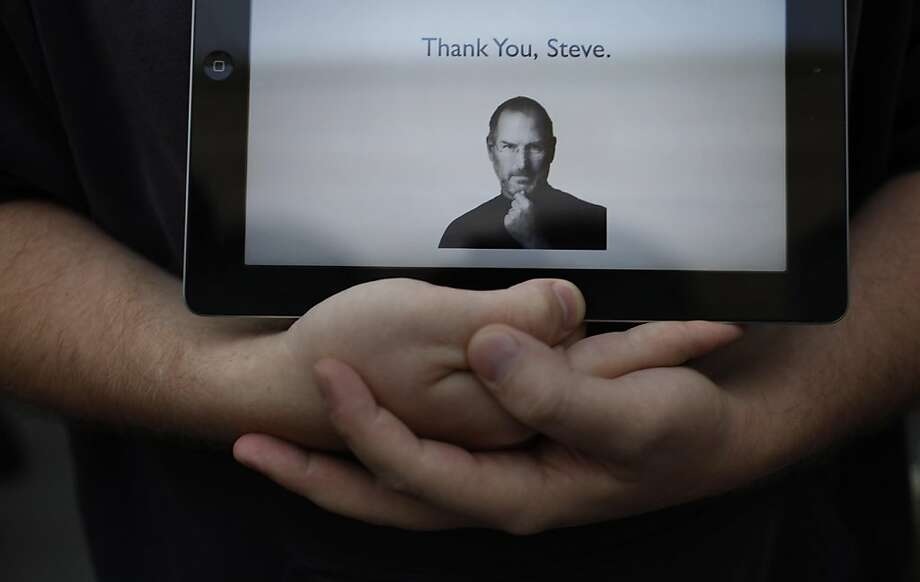 Cory Moll, Apple specialist, stands outside the Apple store on Stockton Street holding an iPad displaying a tribute to Jobs in San Francisco, Calif., on Wednesday, October 5, 2011. Moll has worked at Apple for 4 years, and when he heard the news, came down to the store, creating the tribute to Jobs on the Pages application on his way there. Apple announced the death of Steve Jobs,  the Apple co-founder,  on Wednesday. Photo: Lea Suzuki, The Chronicle