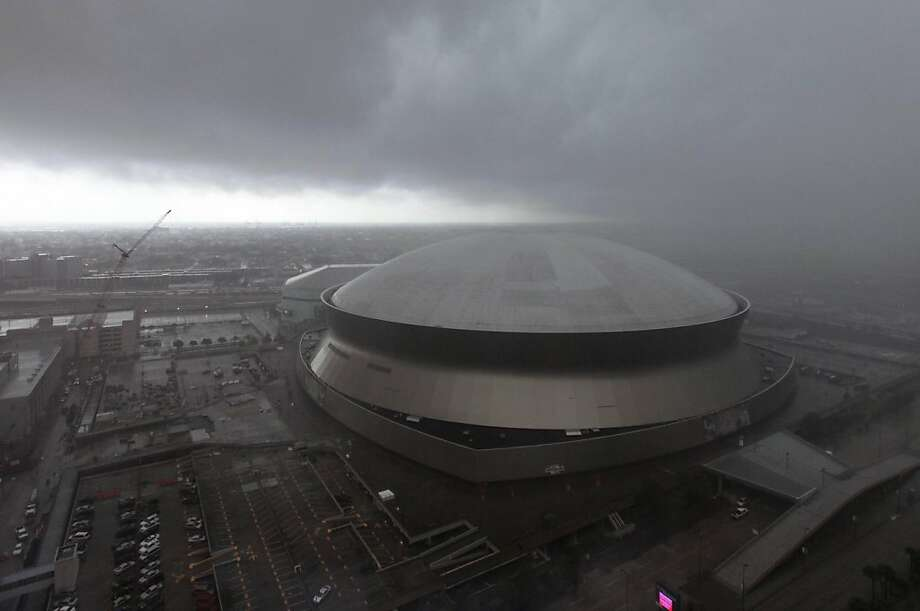 FILE - In this July 25, 2011 file photo, a major rainstorm is seen approaching the Louisiana Superdome in Downtown New Orleans. Once considered the Cadillac of sports stadiums, the venerable Louisiana Superdome will become the Mercedes-Benz Superdome under a naming rights deal to be formally announced on Tuesday. The New Orleans Saints, who hold authority under an agreement with the state to sell naming rights to the Dome, confirmed an agreement with Mercedes-Benz had been reached.  (AP Photo/Gerald Herbert, file) Photo: Gerald Herbert, AP