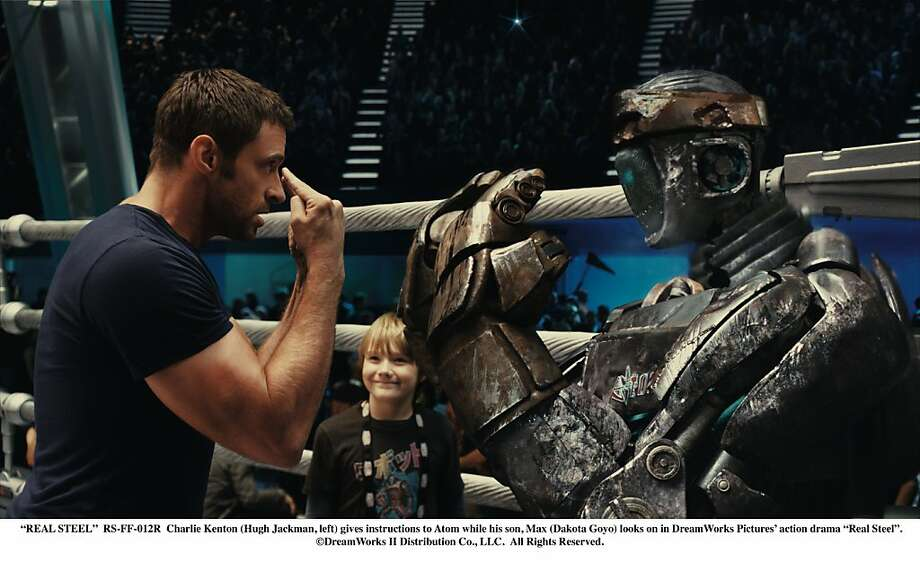 """Charlie Kenton (Hugh Jackman, left) gives instructions to Atom while his son, Max (Dakota Goyo) looks on in DreamWorks Pictures' action drama """"Real Steel"""". ©DreamWorks II Distribution Co., LLC.  All Rights Reserved.  """"REAL STEEL""""  RS-FF-012R  Charlie Kenton (Hugh Jackman, left) gives instructions to Atom while his son, Max (Dakota Goyo) looks on in DreamWorks Pictures' action drama """"Real Steel"""".  ©DreamWorks II Distribution Co., LLC. ÊAll Rights Reserved. Photo: Disney"""