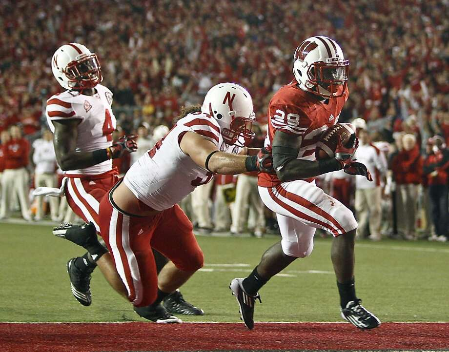 Wisconsin's Montee Ball (28) scores a touchdown against Nebraska's Cameron Meredith, center, and Lavonte David during the second half of an NCAA college football game Saturday, Oct. 1, 2011, in Madison, Wis. (AP Photo/Andy Manis) Photo: Andy Manis, AP