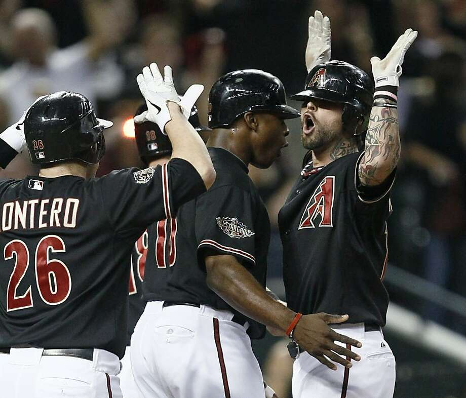 Arizona Diamondbacks' Ryan Roberts, right, is greeted at the plate by teammates following his first-inning grand slam against the Milwaukee Brewers in Game 4 of baseball's National League division series Wednesday, Oct. 5, 2011, in Phoenix. (AP Photo/Matt York) Photo: Matt York, AP