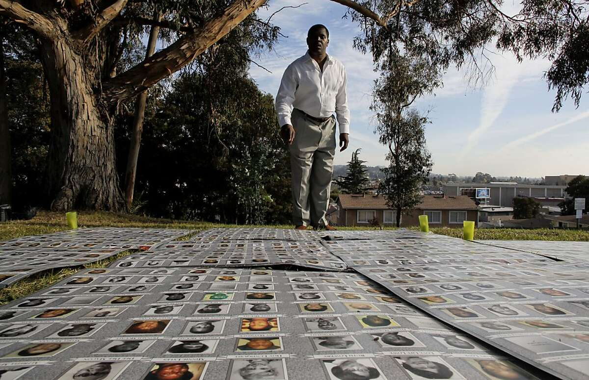 Larry Blufold seaches the photos of victims for the 27 family members that he lost when he was 14-years-old, as family and friends gather for the 32nd anniversary of Jonestown massacre, on Thursday Nov. 18, 2010 at the Evergreen Cemetery in Oakland, Calif., to remember those lost in the mass suicide in Guyana, South America in 1978.