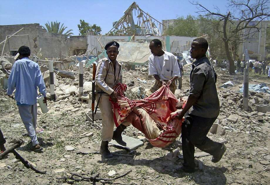 Somalis carry the body of a man killed at the scene of an explosion in Mogadishu, Somalia Tuesday, Oct. 4, 2011. A car laden with explosives blew up in front of the Ministry of Education in the Somali capital Tuesday, killing scores of people in the biggest attack since an Islamist insurgent group withdrew from Mogadishu, a rescue official said. (AP Photo/Farah Abdi Warsameh) Photo: Farah Abdi Warsameh, AP