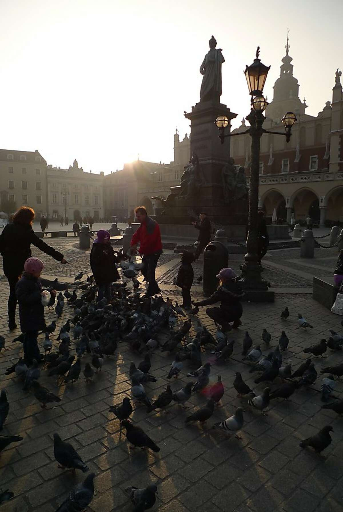 Children feed the ubiquitous pigeons on Market Square as the sun begins to set on Krakow.