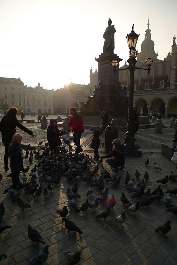 Children feed the ubiquitous pigeons on Market Square as the sun begins to set on Krakow. Photo: Spud Hilton, The Chronicle