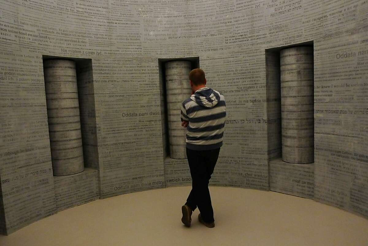 A visitor stands in a room covered floor to ceiling in snippets of stories by Holocaust survivors and Krakow citizens in the Schindler Factory Museum.
