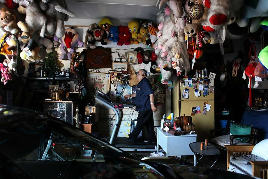 Surrounded by a stuffed animal collection he started 16 years ago, Jose Marquez, goes through his daily treadmill routine while watching Spanish language movies. Photo: Mike Kepka, The Chronicle