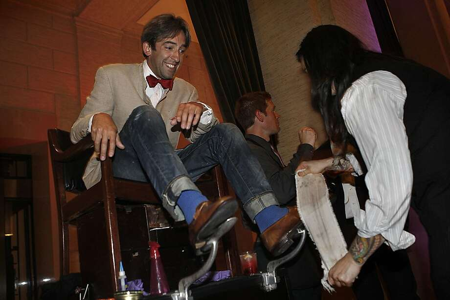 """Max Mason from Oxford, England getting his acid spat shoes shines at the third annual """"Styling the Modern Man"""" event at Bently Reserve in San Francisco, California, on Thursday, September 15, 2011.   He is dressed for a wedding party in a creme Nehru jacket, Gieves & Hawkes bow tie, 666 jeans, and blue socks as Kealani Lada shines his shoes. Photo: Liz Hafalia, The Chronicle"""