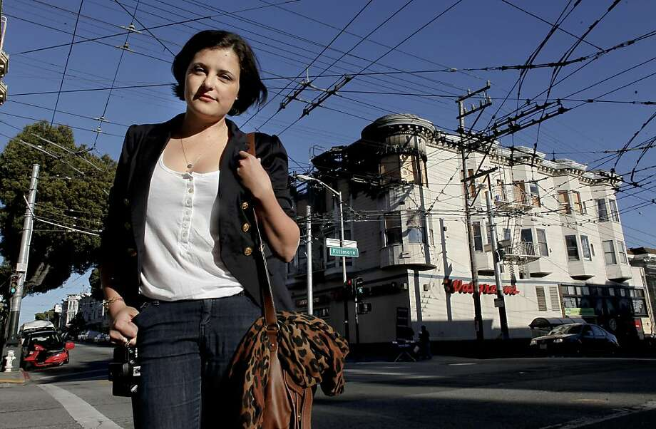 Tiffany Bukowski stands on the corner of Fillmore and Haight Streets, with her apartment building in the background on Friday October 7, 2011, in San Francisco, Ca. Tiffany began a blog about the fire that destroyed the building and left  31 residents without a home. The apartment complex community pulled together collecting cloths, held a fund raiser and collected donations while city agencies were bogged down in red tape with assistance. Photo: Michael Macor, The Chronicle