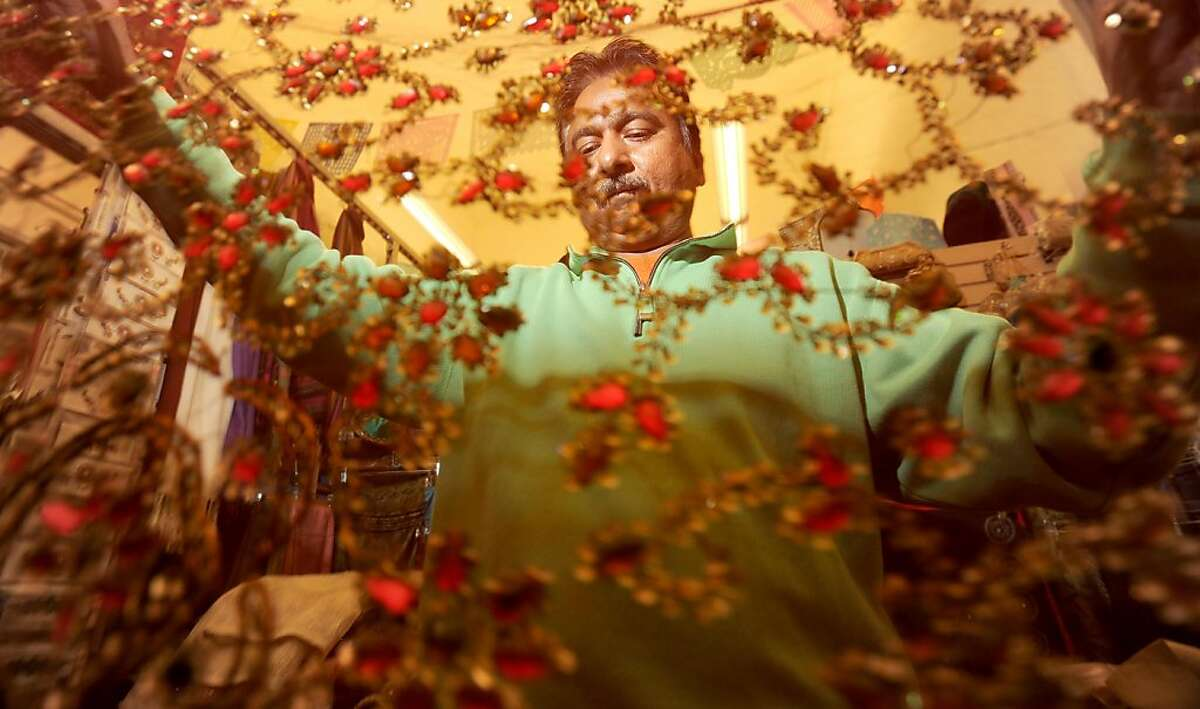 Raju Kumar folds tablecloths in preparation for his store's grand opening on Tuesday, Oct. 4, 2011, in San Francisco