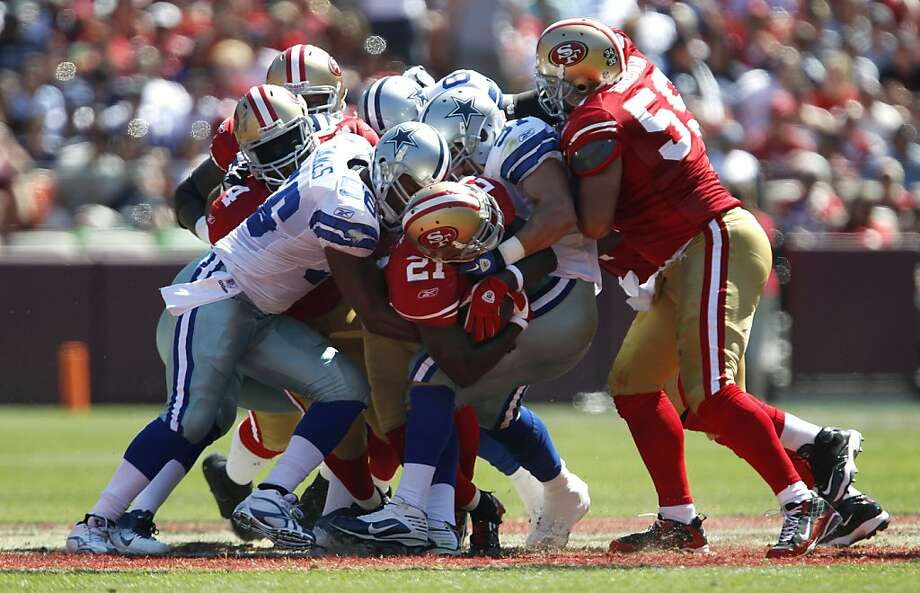 San Francisco 49ers running back Frank Gore (21) is tackled by Dallas Cowboys defenders in the first quarter of an NFL football game in San Francisco, Sunday, Sept. 18, 2011. (AP Photo/Tony Avelar) Photo: Tony Avelar, AP