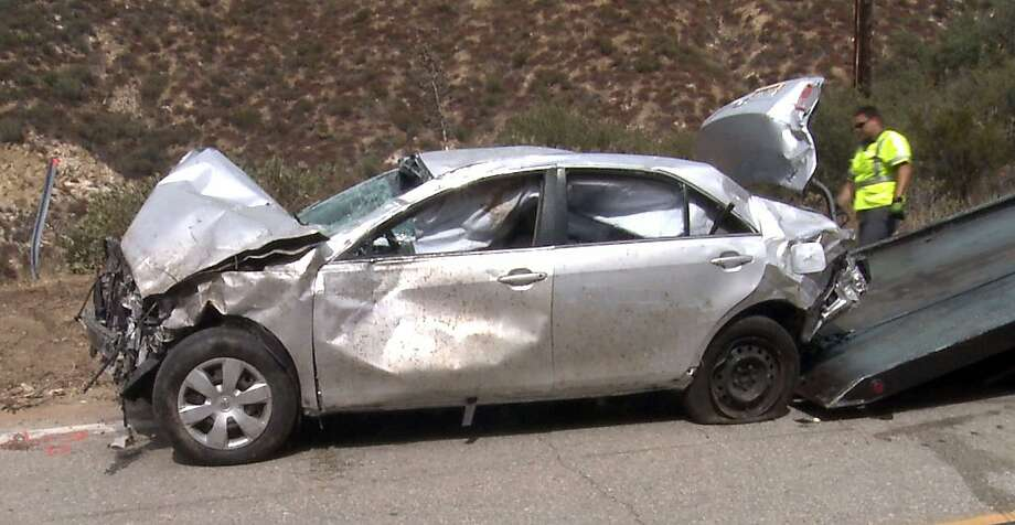 This video image provided by APTN shows a vehicle that contained a body being removed after it was taken from a crash site where another crash survivor, David Lavau was found after surviving six days, in the Angeles National Forest near Los Angeles Friday Sept. 30, 2011. This car, a Toyota Camry, was identified as belonging to 88-year-old Melvin Gelfand, whose family had reported him missing on Sept. 14. (AP Photo/APTN) Photo: AP