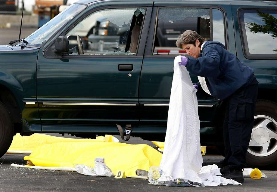 A San Leandro police officer covered one of the deceased with a white sheet while they waited for the coroner to arrive. Three people lost their lives in San Leandro, Calif. outside a warehouse where a party was held early Sunday morning, October 2, 2011. Photo: Brant Ward, The Chronicle
