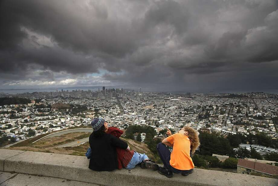 Juliet Martine and her children, Harmony Baker (right), 11, and Jasper Baker (middle), 8, look at storm clouds in the skyline from Twin Peaks in San Francisco, California, on Thursday, October 6, 2011. Photo: Craig Lee, Special To The Chronicle