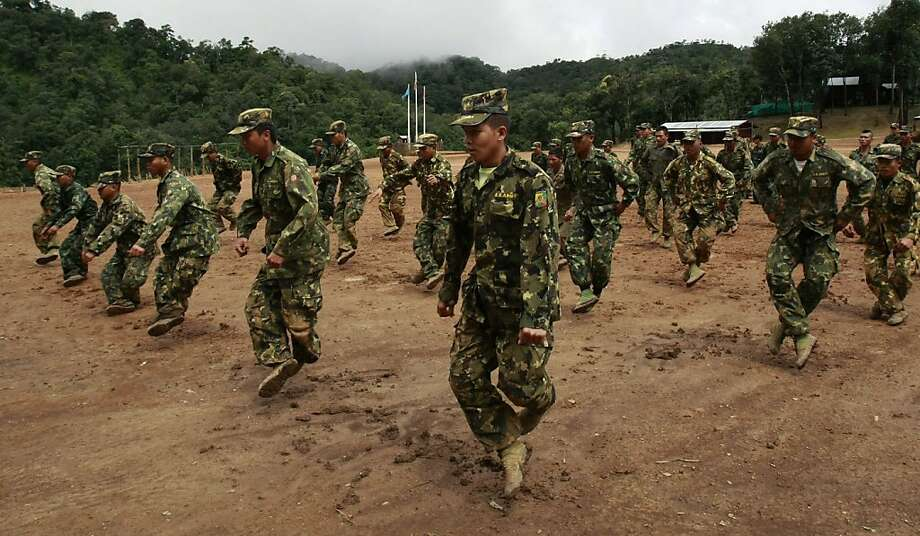 ADVANCE FOR USE SUNDAY, SEPT. 25, 2011 AND THEREAFTER - In this Friday, Aug. 19, 2011 photo, fighters of the Shan State Army train at a forest base near the rebel headquarters of Loi Tai Leng in Myanmar's Shan state. The Shan, along with other minority groups, have been fighting against the Myanmar government for greater autonomy for decades. An upsurge in violence comes amid an unprecedented flood of foreign investment in lucrative dam and pipeline projects, much of it from resource-hungry China. Critics say commercial interests are trumping human rights concerns. The government denies such claims, arguing the nation must develop. (AP Photo/Apichart Weerawong)  Ran on: 10-02-2011 The Shan State army trains at a forest base near the rebel headquarters of Loi Tai Leng, Burma. Photo: Apichart Weerawong, AP