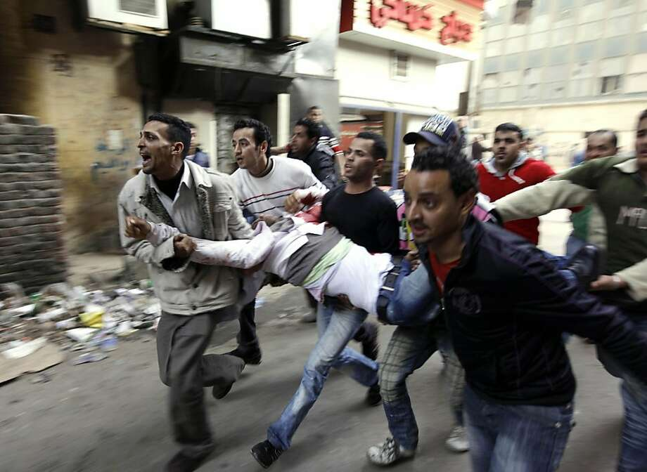 Egyptians carry an injured  protester during clashes with anti-riot police in Cairo, Egypt, Saturday, Jan. 29, 2011. Hundreds of anti-government protesters have returned to Cairo's central Tahrir Square, chanting slogans against Hosni Mubarak just hours after the Egyptian president fired his Cabinet but refused to step down. (AP Photo/Ben Curtis) Ran on: 01-30-2011 Egyptians carry an injured protester during clashes with anti-riot police in Cairo. When the troops rolled in, the police pulled back from the protests. Photo: Ben Curtis, AP