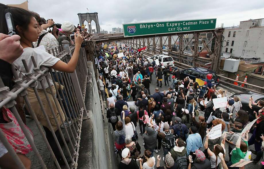 NEW YORK, NY - OCTOBER 01: Supporters (L) cheer from the pedestrian walkway as demonstrators affiliated with the Occupy Wall Street movement attempt to cross the Brooklyn Bridge on the motorway on October 1, 2011 in New York City. The motorway portion of the bridge is not intended for pedestrians and as the marchers attempted to cross, they were stopped midway by police. Hundreds of protesters were arrested.  (Photo by Mario Tama/Getty Images) Photo: Mario Tama, Getty Images