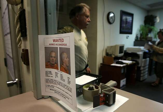 Mendocino Conty Sheriff Tom Allman walks past a wanted poster of the suspect at headquarters in Fort Bragg, Ca. Law enforcement  intensified their search for murder suspect Aaron Bassler a day after a shootout between police officers and the suspect in an unincorporated area of Mendocino County near Northspur, Ca. on Friday September 30, 2011. Photo: Michael Macor, The Chronicle