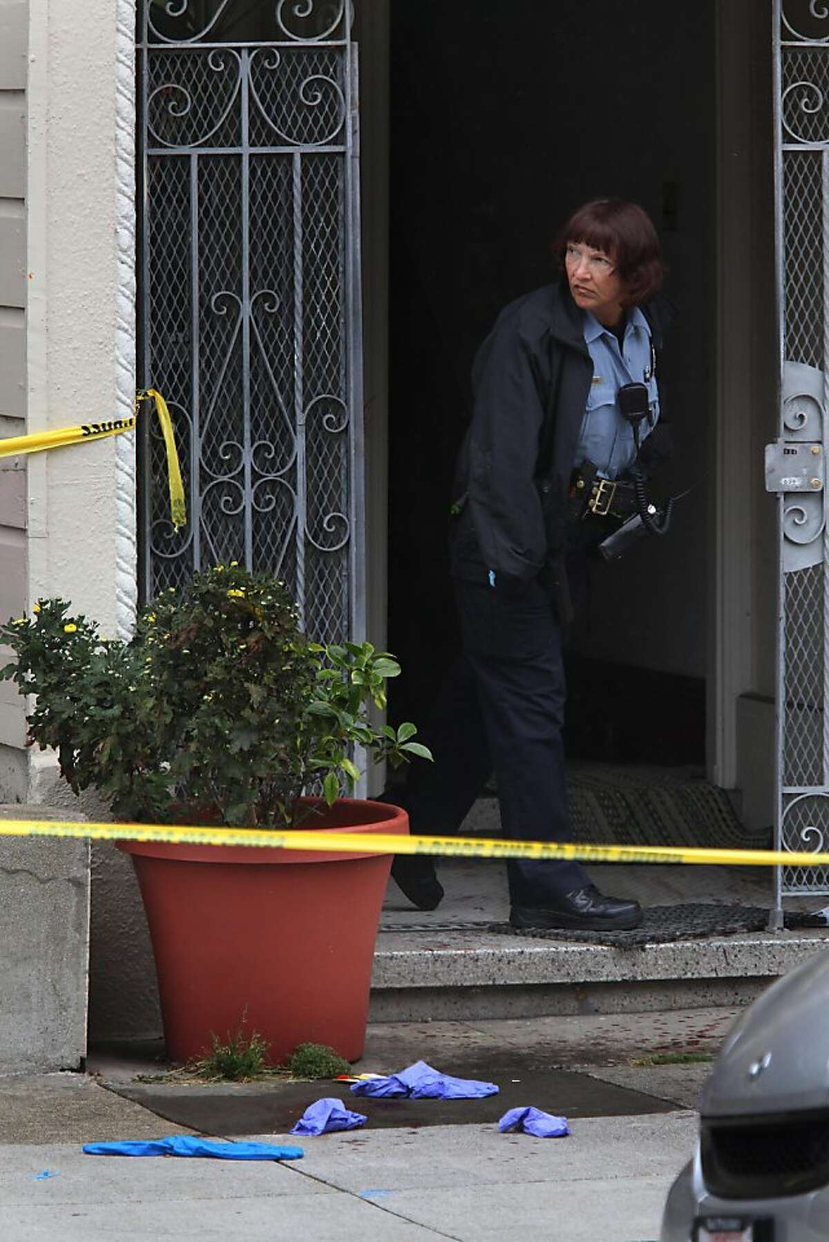 An officer peers out of the doorway where police shot and killed a knife-wielding man in the Richmond District this morning in San Francisco, Calif., on Monday, October 3, 2011. The man stabbed one elderly relative to death and wounded another, police said.