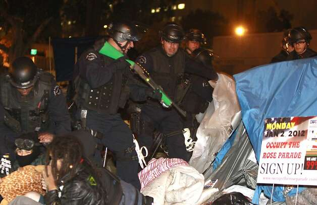 Los Angeles Police inspect a tent with guns that fire rubber bullets at the Occupy Los Angeles encampment at Los Angeles city hall early Wednesday morning, Nov. 30, 2011. Police in Los Angeles and Philadelphia stormed Occupy Wall Street encampments in both cities Wednesday, demanding protestors leave demonstration sites. (AP Photo/Mark Boster, Pool) Photo: Mark Boster, AP