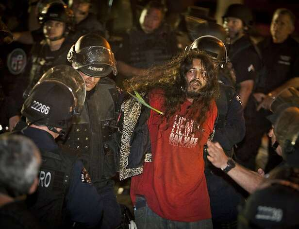 Los Angeles Police officers arrest an Occupy Los Angeles supporter at the camp at the Los Angeles City Hall, Wednesday, Nov. 30, 2011, in Los Angeles.   In a massive show of force, 1,400 police officers, some in riot gear stormed the Occupy Los Angeles camp early Wednesday, driving protesters from the park and arresting more than 200 who defied orders to leave.  (AP Photo/Bret Hartman) Photo: Bret Hartman, AP