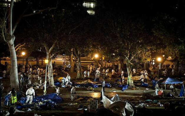 Los Angeles Police officers clean up the debris left by the Occupy Los Angeles supporters after the LAPD raided their camp at the Los Angeles City Hall, Wednesday, Nov. 30, 2011, in Los Angeles.   In a massive show of force, 1,400 police officers, some in riot gear stormed the Occupy Los Angeles camp early Wednesday, driving protesters from the park and arresting more than 200 who defied orders to leave.  (AP Photo/Bret Hartman) Photo: Bret Hartman, AP