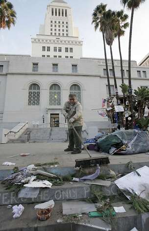 City worker Gino Rodriguez helps with the cleanup outside Los Angeles City Hall on Wednesday, Nov 30,  2011. More than 1,400 police officers, some in riot gear, cleared the Occupy Los Angeles camp early Wednesday, driving protesters from a park around City Hall and arresting more than 200 who defied orders to leave. (AP Photo/Nick Ut) Photo: Nick Ut, AP