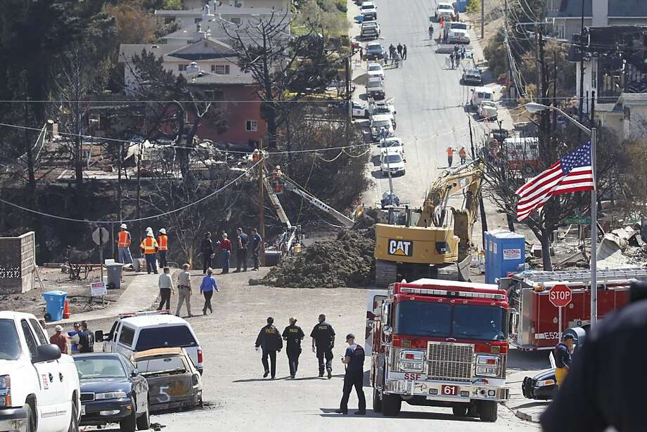 Utility workers connect  power lines over the hole where the explosion occurred, Monday Sept. 13, 2010, in San Bruno, Calif. Photo: Lacy Atkins, The Chronicle