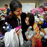 Evacuees Melah Alash and her 9-year-old daughter, Sara, pick up some donated items at the Veterans Memorial Recreation Center after evacuating their San Bruno home.