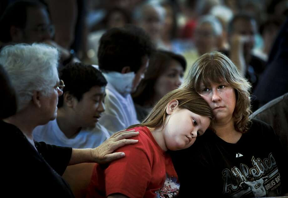 Jessica Sherwin, 11, is comforted by her mom, Michelle, and others at a community meeting. Photo: Michael Macor, The San Francisco Chronicle