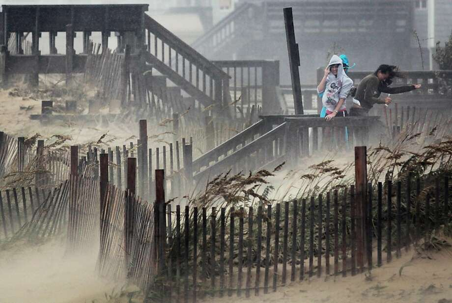 KILL DEVIL HILLS, NC - AUGUST 27:  People shield themselves from blowing sand and rain as they look over the beach during Hurricane Irene August 27, 2011 in Kill Devil Hills, North Carolina. Hurricane Irene hit Dare County, which sits along the Outer Banks and includes the vacation towns of Nags Head, Kitty Hawk and Kill Devil Hills, as a category one hurricane around mid-day today.  (Photo by Scott Olson/Getty Images) Ran on: 08-28-2011 People shield themselves from winds and sand hurled by Hurricane Irene in Kill Devil Hills, N.C. Ran on: 08-28-2011 People shield themselves from winds and sand hurled by Hurricane Irene in Kill Devil Hills, N.C. Photo: Scott Olson, Getty Images