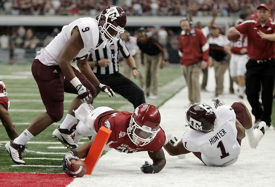 Arkansas running back Ronnie Wingo Jr. (20) get past Texas A&M  linebacker Charlie Thomas (9) and defensive back Trent Hunter to score a touchdown during the second half of an NCAA college football game at Cowboys Stadium on Saturday, Oct. 1, 2011, in Arlington, Texas. Arkansas won 42-38. (AP Photo/Brandon Wade) Photo: Brandon Wade, AP