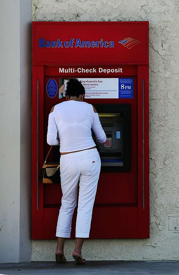 LOS ANGELES, CA - SEPTEMBER 29:  A customer uses a Bank of America ATM on September 29, 2011 in Los Angeles, California. Bank of America annouced its plans to start charging a $5 monthly fee for customers using their debit card for purchases starting early in 2012.  (Photo by Kevork Djansezian/Getty Images)  Ran on: 10-01-2011 A customer uses a Bank of America ATM in L.A. Photo: Kevork Djansezian, Getty Images