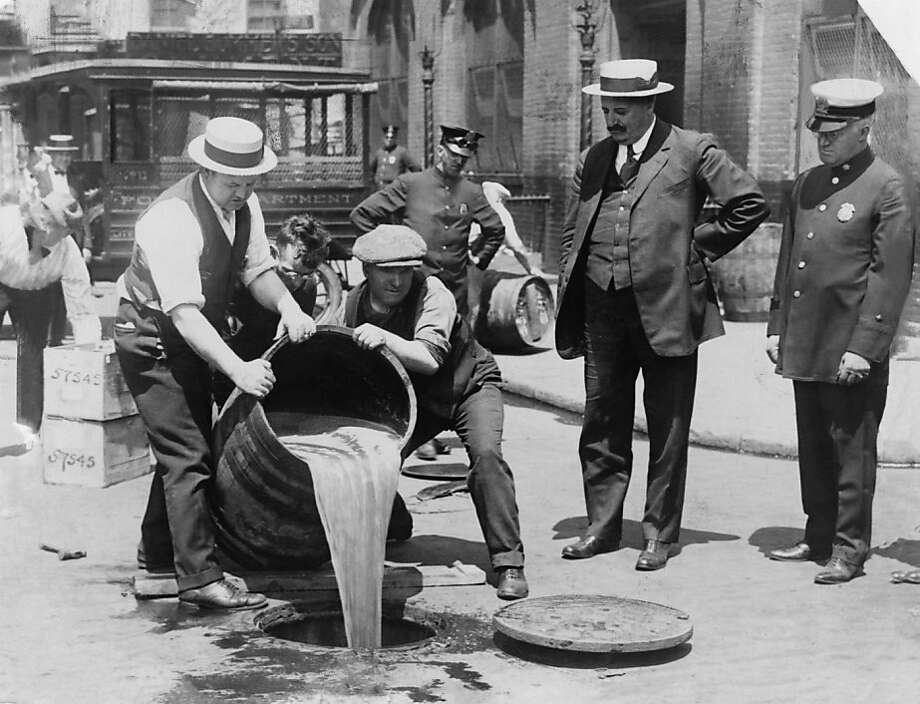 "An undated handout photo of New York City police official watching agents pour liquor into a sewer following a raid during the Prohibition era, around 1921. The new PBS documentary ""Prohibition"" explores the roots of the 18th Amendment banning alcohol sales, wedge-issue politics and legislating morality. (Library of Congress, Prints & Photographs Division via The New York Times) -- EDITORIAL USE ONLY. -- PHOTO MOVED IN ADVANCE AND NOT FOR USE - ONLINE OR IN PRINT - BEFORE SEPT. 25, 2011.   Ran on: 10-01-2011 A New York City police official watches agents pour liquor into a sewer around 1921. The documentary &quo;Prohibition&quo; explores the era. Photo: Library Of Congress, Prints, NYT"